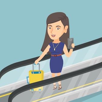 Frau, die smartphone auf rolltreppe am flughafen verwendet