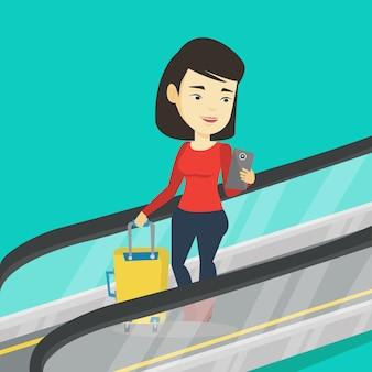Frau, die smartphone auf rolltreppe im flughafen verwendet.