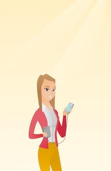 Frau, die smartphone von der tragbaren batterie wieder auflädt