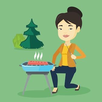 Frau, die steak auf grill grillt.