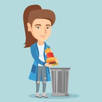 Frau, die ungesunde fertigkost in den abfalleimer wirft.