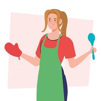 Frau, die unter verwendung der schürze mit löffel und handschuh kocht