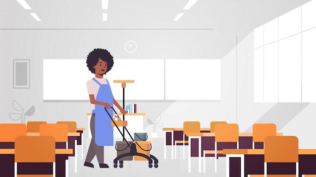 Frau, die wagen mit vorräten schiebt weiblicher reiniger hausmeister im einheitlichen reinigungsdienstkonzept moderne schulklassenrauminnenraum in voller länge horizontal