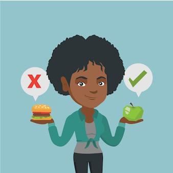 Frau, die zwischen hamburger und kleinem kuchen wählt.