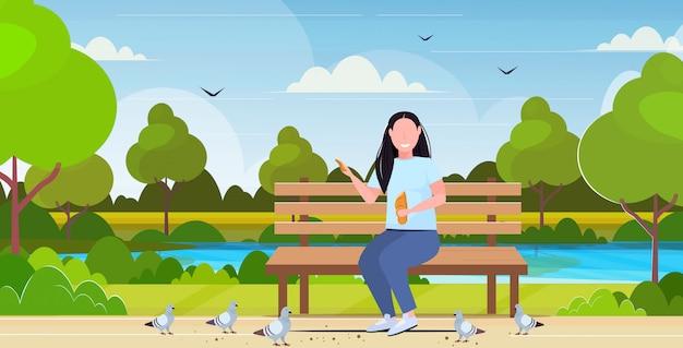 Frau hält brot und füttert herde von tauben übergewichtigen mädchen sitzen holzbank spaß im freien öffentlichen park landschaft hintergrund flach in voller länge horizontal