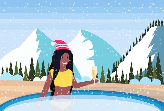 Frau hält champagnerglas im thermischen jacuzzi im freien in den bergen
