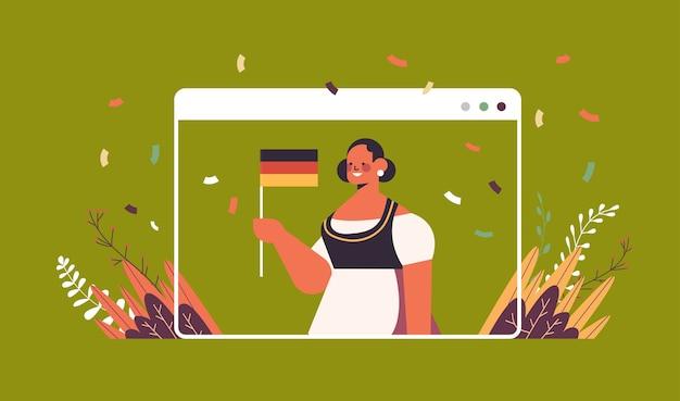 Frau hält deutschland flagge oktoberfest party feier konzept mädchen in traditioneller kleidung mit spaß webbrowser fenster