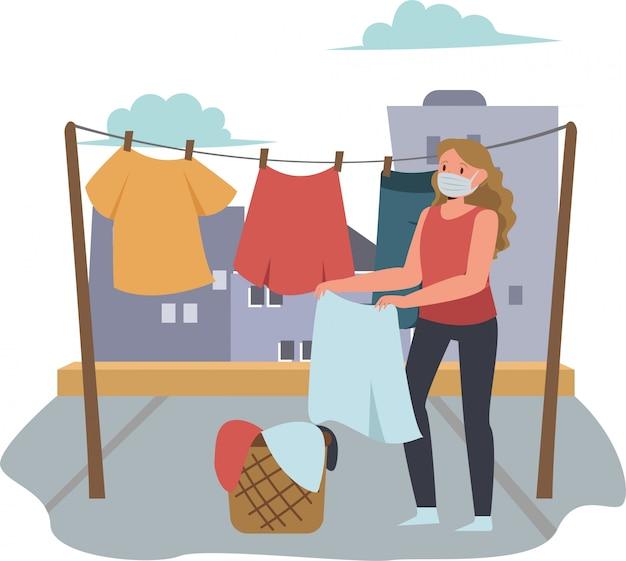Frau hängt ihre wäsche draußen auf, während sie medizinische maske benutzt