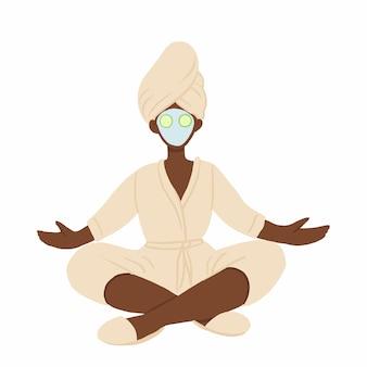 Frau im bademantel, im handtuch und in der gesichtsmaske, die in lotushaltung meditieren.