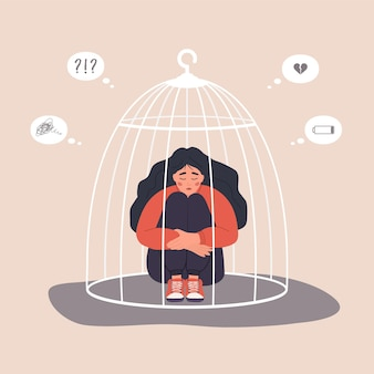 Frau im käfig eingesperrt. unglückliche weibliche figur, die auf dem boden sitzt und knie umarmt.