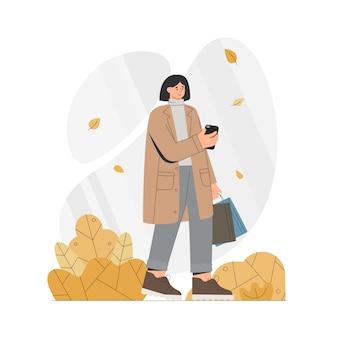 Frau im mantel hält ein telefon und taschen im herbst.