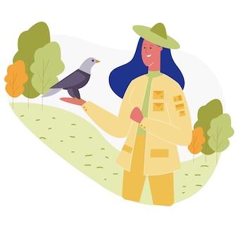 Frau im tierpark, der den vogel an hand sitzt bewundert
