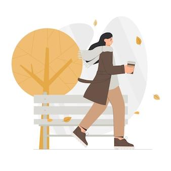 Frau im warmen mantel hält kaffee und geht in den herbstpark.