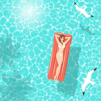 Frau im weißen bikini auf roter luftmatratze