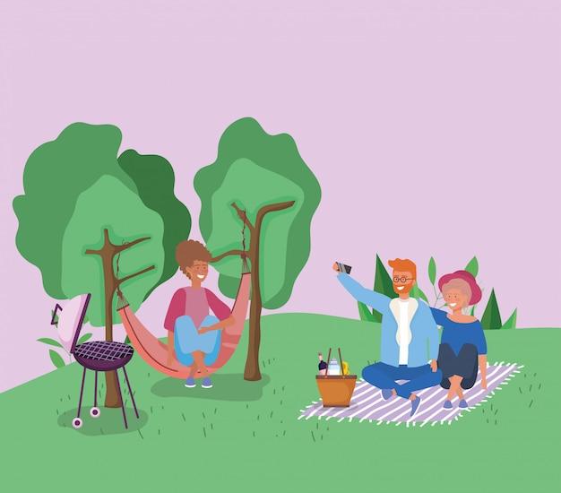 Frau in der hängematte und in paaren, die im umfassenden picknick nimmt selfie sitzen