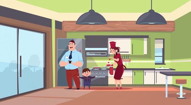 Frau in der koch-uniform, die dem mann und dem jungen im modernen küchen-hintergrund kuchen gibt