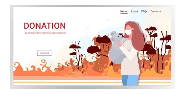 Frau in der maske hält koalabär waldbrände tiere, die im verheerenden buschfeuer naturkatastrophe sterben beten für australien spendenkonzept intensive orange flammen horizontale porträt kopie raum