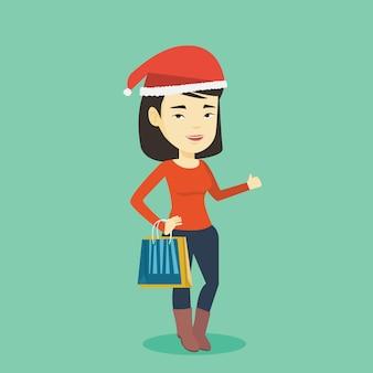 Frau in der weihnachtsmütze, die für weihnachtsgeschenke einkauft.