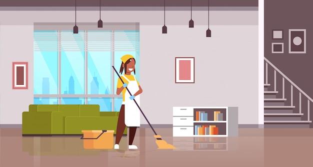 Frau in handschuhen und schürze, die bodenmädchen mit mopphausfrau wäscht, die hausarbeitsreinigungskonzept moderne wohnung wohnzimmerinnenraum horizontal in voller länge tut