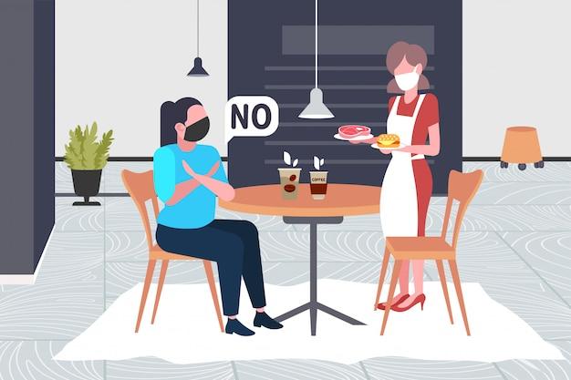 Frau in maske, die kreuzarme tut, sagt nein zu kellnerin mit fleisch und burger, um coronavirus-epidemie zu verhindern mers-cov-virus wuhan 2019-ncov gesundheitsrisiko konzept restaurant interieur in voller länge horizontal