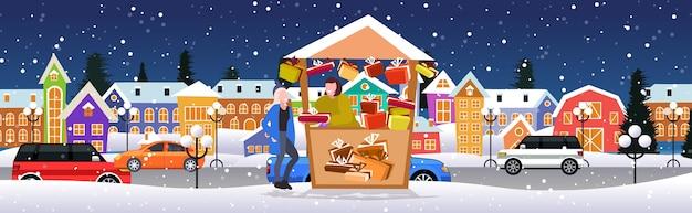 Frau kauft geschenkbox in geschenken stall weihnachtsmarkt wintermesse konzept frohe weihnachten feiertage moderne stadt straße stadtbild hintergrund voller länge skizze horizontale vektor-illustration