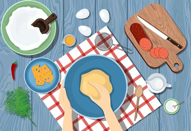 Frau knetet den teig auf einem blauen tisch. sicht von oben. pizza kochen. zutaten auf dem tisch. abbildung