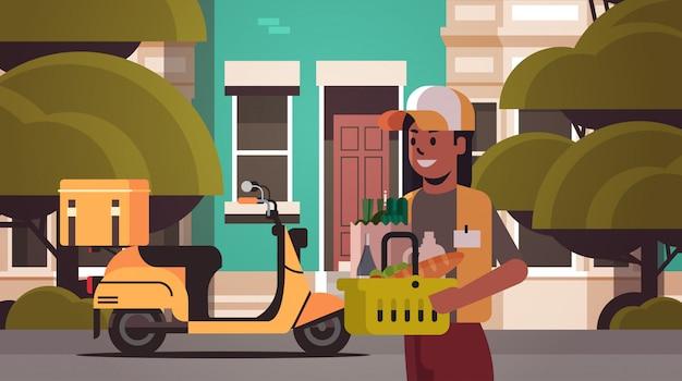Frau kurier holding korb mit lebensmitteln express lebensmittel lieferung von shop oder restaurant konzept modernes haus gebäude außen flach horizontales porträt