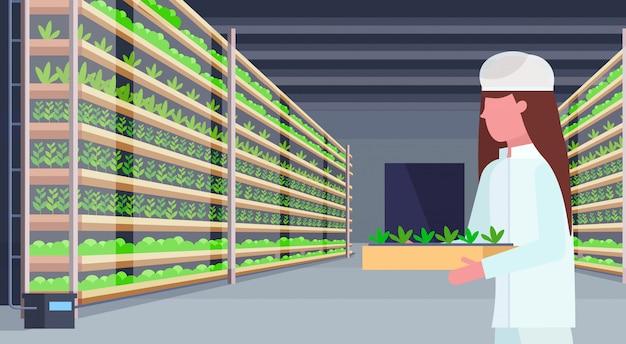 Frau landwirtschaftsingenieur in uniform hält topfpflanzen moderne organische vertikale farm innenlandwirtschaft industrie konzept horizontales porträt