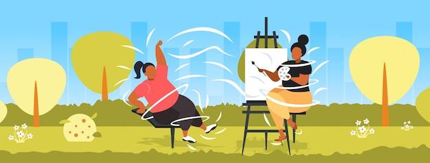 Frau malt porträt des fettleibigen fetten mädchenmodells, das auf stuhlkünstlerzeichnung auf leinwand an der staffelei kreative kunsthobby-fettleibigkeitskonzeptstadtparklandschaft aufwirft