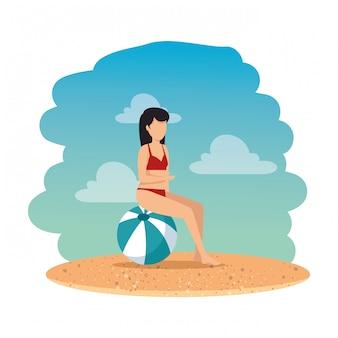 Frau mit badeanzug im ballon am strand sitzen