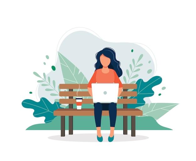 Frau mit dem laptop, der auf der bank in der natur und in den blättern sitzt.