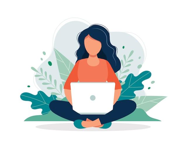 Frau mit dem laptop, der in der natur und in den blättern sitzt