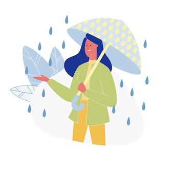 Frau mit dem punktierten hellen regenschirm, der am regen steht