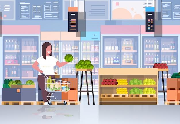 Frau mit einkaufswagen, der gemüse- und obstgewichtsverlustkonzept wählt