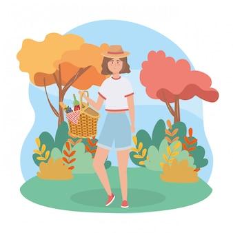 Frau mit korblebensmittel- und -weinflasche und -trauben