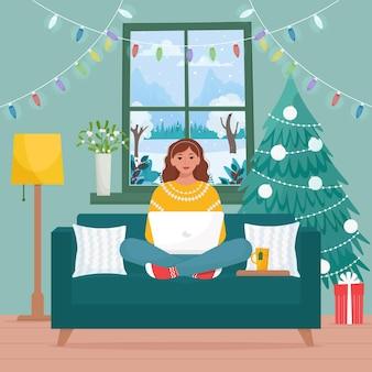 Frau mit laptop sitzt auf dem sofa im dekorierten haus zum weihnachtsfeiertag nette vektorillustration