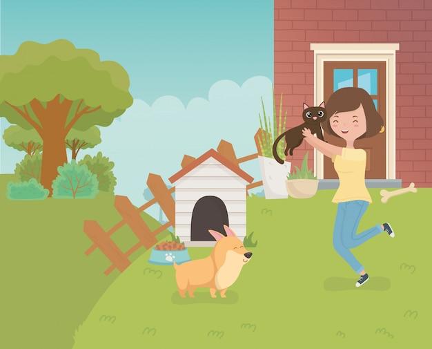 Frau mit netter kleiner katze und hund im hausgarten
