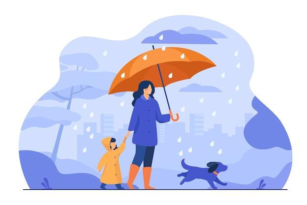 Frau mit regenschirm, mädchen im regenmantel und hund, die im regen im stadtpark gehen. vektorillustration für familienaktivität, schlechtes wetter, regengusskonzept