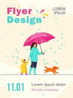 Frau mit regenschirm, mädchen im regenmantel und hund, die im regen in der stadtparkfliegervorlage gehen