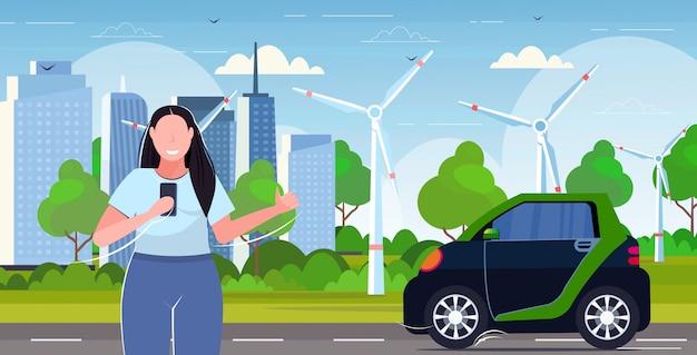 Frau mit smartphone mobile app online bestellen taxi mädchen fangen auto carsharing konzept transportservice moderne windturbinen stadtbild hintergrund horizontales porträt