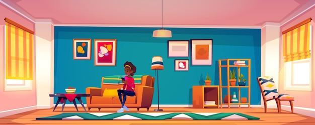 Frau mit smartphone sitzt auf sofa zu hause. afroamerikanermädchen mit dem mobiltelefon in der hand, die auf der couch entspannt elektronikbuch oder nachrichten in den sozialen netzwerken liest