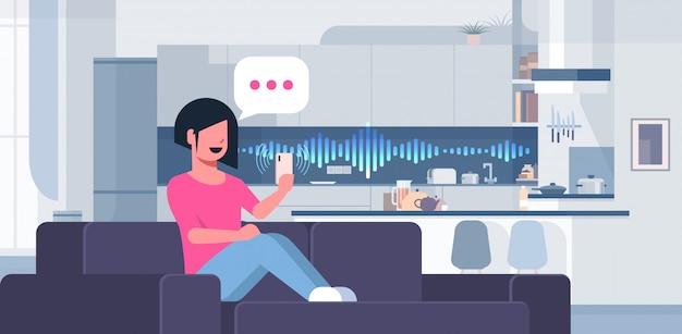 Frau mit smartphone smart speaker spracherkennungskonzept chat blase kommunikation moderne küche interieur flach horizontal in voller länge