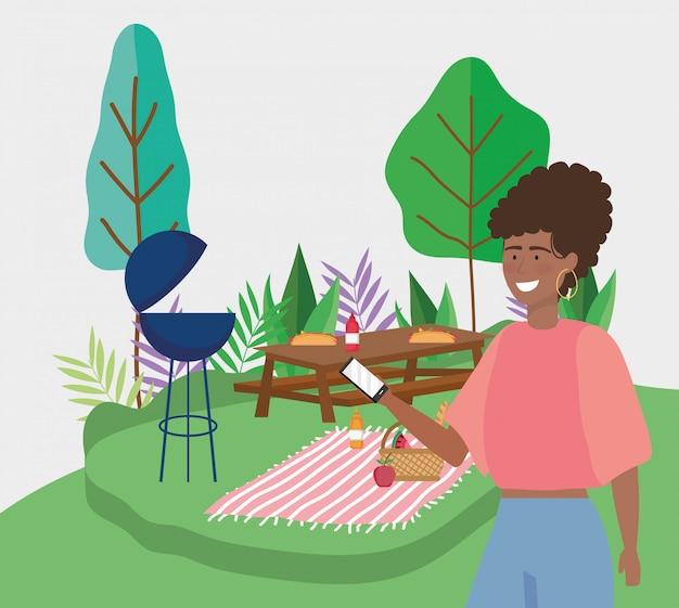 Frau mit smartphonetablettengrilllebensmittel-deckenpicknick