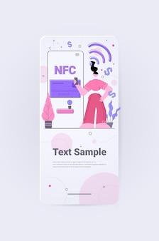 Frau mit zahlungsautomat und mobiltelefon mit kreditkarte auf smartphones kontaktlose zahlung erfolgreiche nfc-transaktion