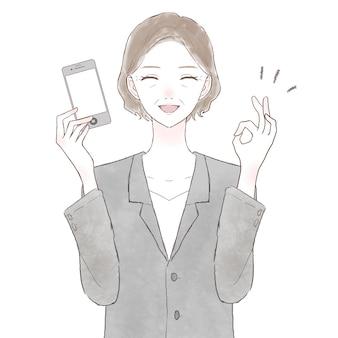 Frau mittleren alters, die einen anzug trägt, der ein smartphone hält und ein ok-zeichen hält. auf weißem hintergrund.