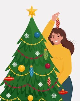 Frau schmückt einen weihnachtsbaum. nette vektorillustration im flachen stil