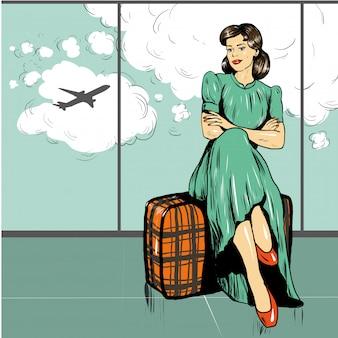 Frau sitzen auf einer tasche im flughafen, der auf einen flug wartet