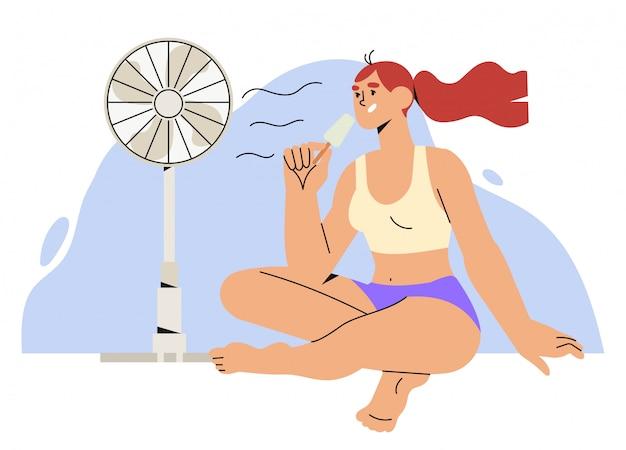 Frau sitzen mit elektrischem luftventilator.