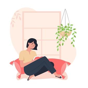 Frau sitzt am fenster und liest ein buch