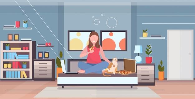 Frau sitzt auf dem bett mit katze übergewichtiges mädchen, das pizza mit laptop ungesunde ernährung fettleibigkeit konzept moderne wohnung schlafzimmer interieur wohnung in voller länge horizontal isst